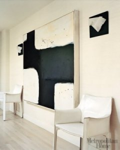 Cassina's Cab chairs by Mario Bellini in white leather; black-and-white abstract painting