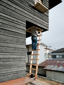 The Coal House outdoor tea room ladder contrasts with the charred siding.