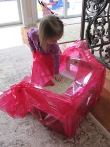 My niece unwraps her cellophane covered birthday gift.
