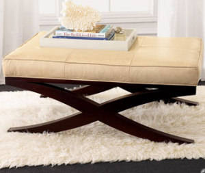 Pear leather and a polished wooden base gives this ottoman sophisticated charm.  |  Neiman's
