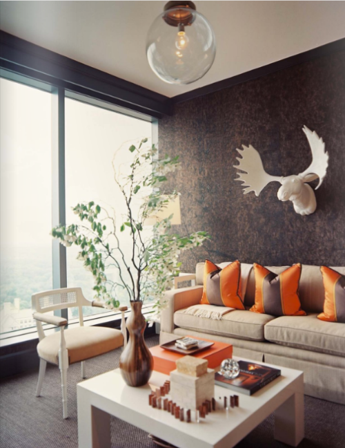 Cork wallpaper dampens sound in the den creating a perfect getaway. Nail heads, suede, and a glossy white moose give it all a unexpected rustic charm.