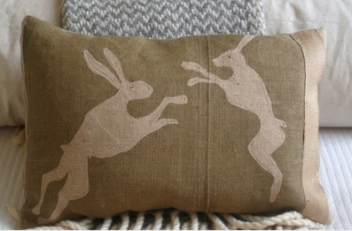 Inspired by the countryside and folklore, these leaping hares are playing on a hessian rustic ochre background with an applique on back., $56