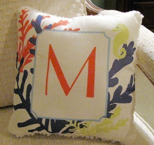 This custom monogrammed tiny pillow is adorned with multi-color coral and seahorses and a white chenille backside.