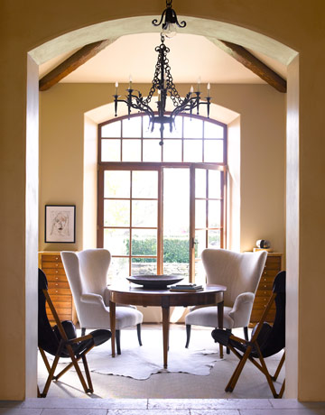 The leather chairs add a hint of black, smooth texture, and a lived in look to the bright dining room
