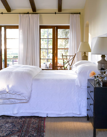 Crisp white bedding, layered floor coverings, and an artistic chair breathe fresh air from the stained wood french doors.