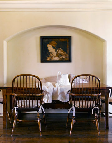 Simple chairs and symmetrical seating is flanked by a moody oil painting.