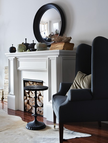 The mantel comes to life with a rugged display of firewood, a subtle rug, pale pumpkins and black gourd vases.