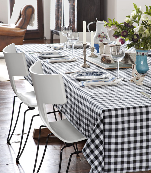 Contemporary white and black stacking chairs contrast with the black and white checked tablecloth. Find similar chairs at Wrest Elm for under $100 each!