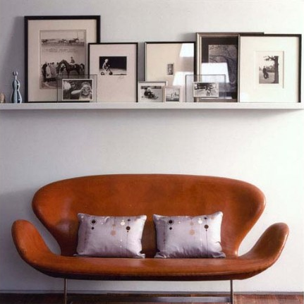 frames and objects on a wall shelf